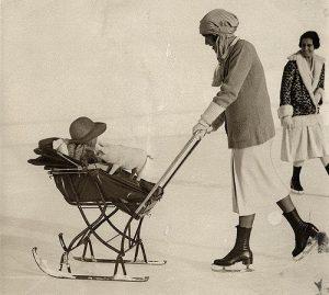 Kinderwagen op ski's (slee) op het ijs, voortgeduwd door moeder op schaatsen. Moeder draagt (onpraktische) schaatskleding en de baby vermaakt zich met een speelgoed varkentje. St. Moritz, Zwitserland, 1926.